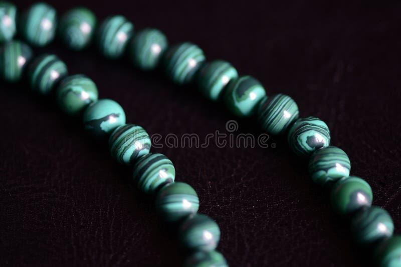 Collana di pietra delle perle della malachite su un fondo scuro immagine stock libera da diritti