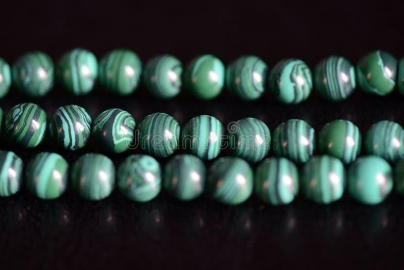 Collana di pietra delle perle della malachite su un fondo scuro immagine stock
