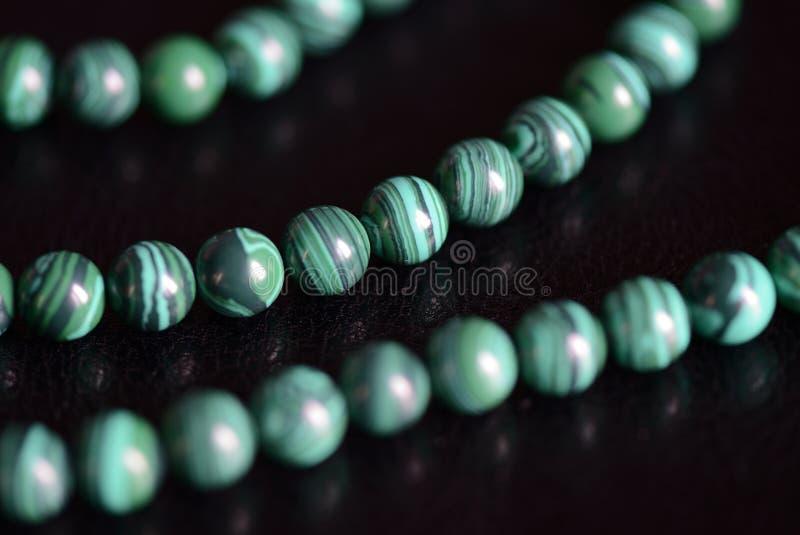 Collana di pietra delle perle della malachite su un fondo scuro fotografie stock