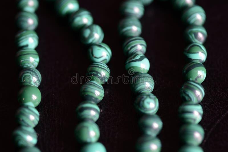 Collana di pietra delle perle della malachite su un fondo scuro immagini stock