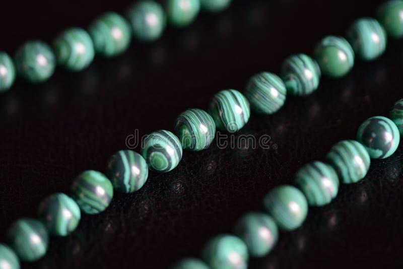 Collana di pietra delle perle della malachite su un fondo scuro fotografia stock