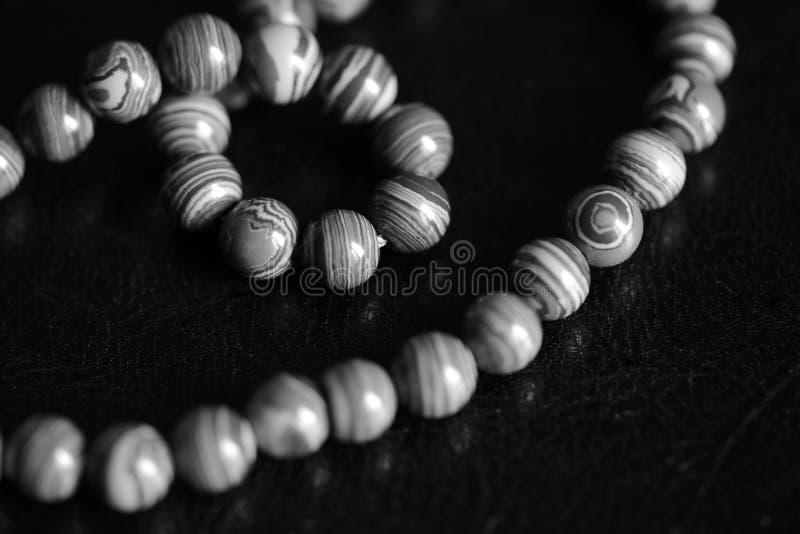 Collana di pietra delle perle della malachite su un fondo scuro Rebecca 36 fotografie stock