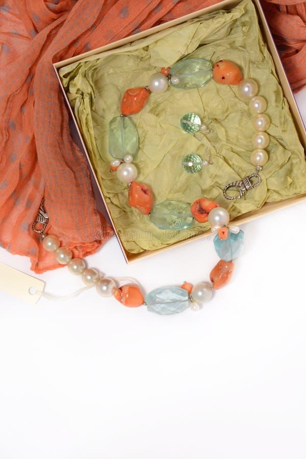 Collana ed orecchini delle pietre naturali su un fondo bianco nella scatola con la sciarpa rossa immagini stock libere da diritti