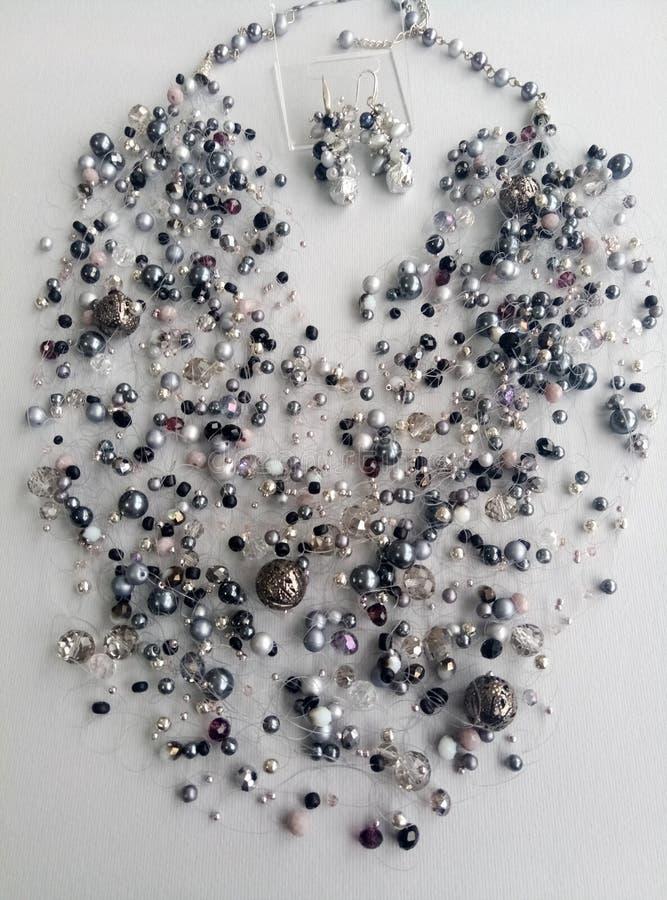 Collana ed orecchini grigi sui precedenti fotografia stock