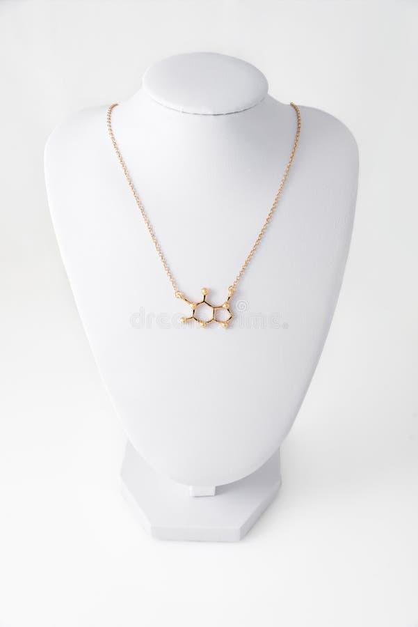 Collana nella forma del molelule della caffeina fatta di oro sul supporto bianco Accessori di lusso delle donne fotografie stock