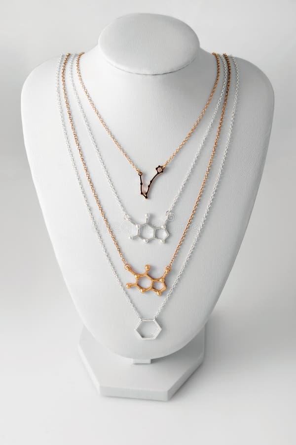 Collane nella forma dei pesci della costellazione e del molelule fatti di oro e di argento sul supporto bianco Accessori di lusso immagine stock