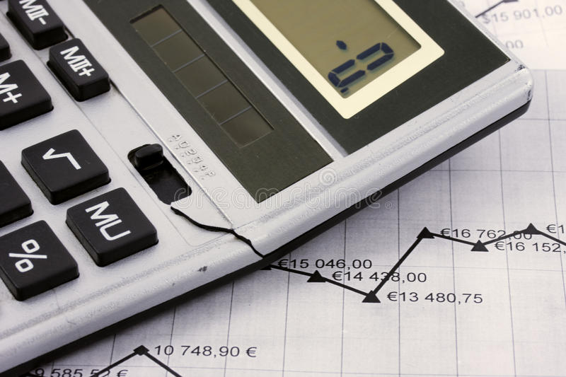 Collaps. Broken calculator on the paper with graph royalty free stock images