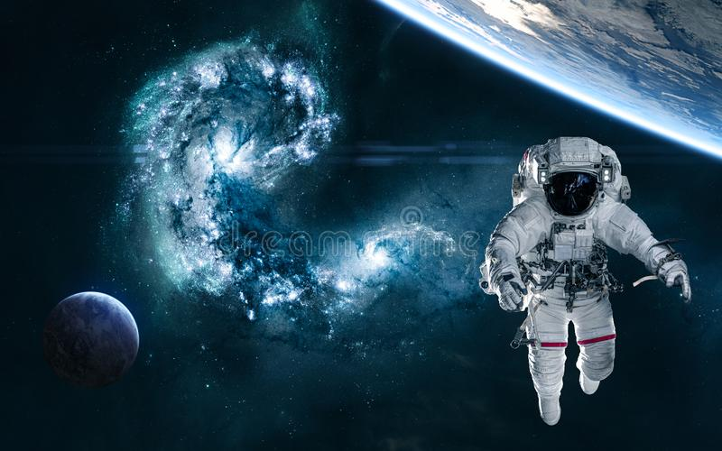 The collapse of galaxies. Astronaut, planets in deep space against background of collision of galaxies in blue tones royalty free stock images