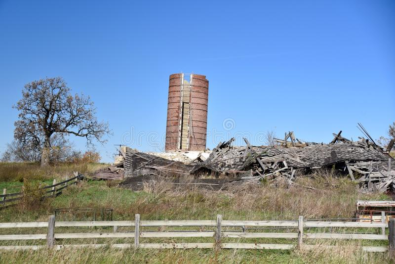 A Collapsed Barn. This is a Fall picture of a collapsed barn and a damaged silo located in Rock County, Wisconsin. This pictu e was taken on October 25, 2015 stock photography