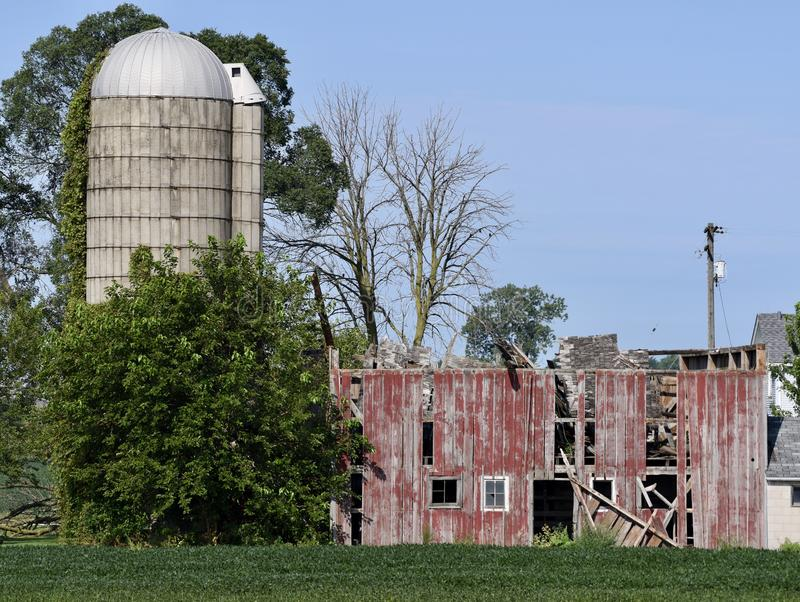 Collapsed Barn Roof. This is a Summer picture of a weathered, dilapidated barn whose roof has collapsed located in Peotone, Illinois in Will County. This picture stock photo