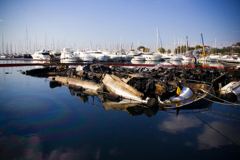 Collapsed boats. Burned, collapsed boats in a marina stock photos