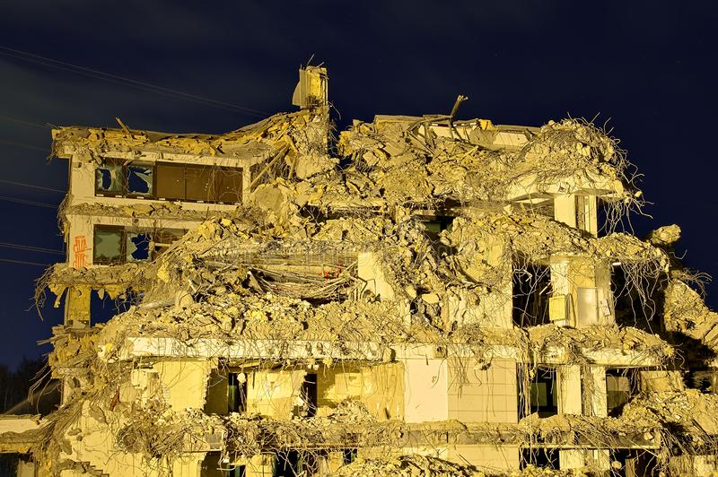 Collapsed building. Collapsed large office building with interior rooms visible. Only rear wall still with broken windows standing royalty free stock photos