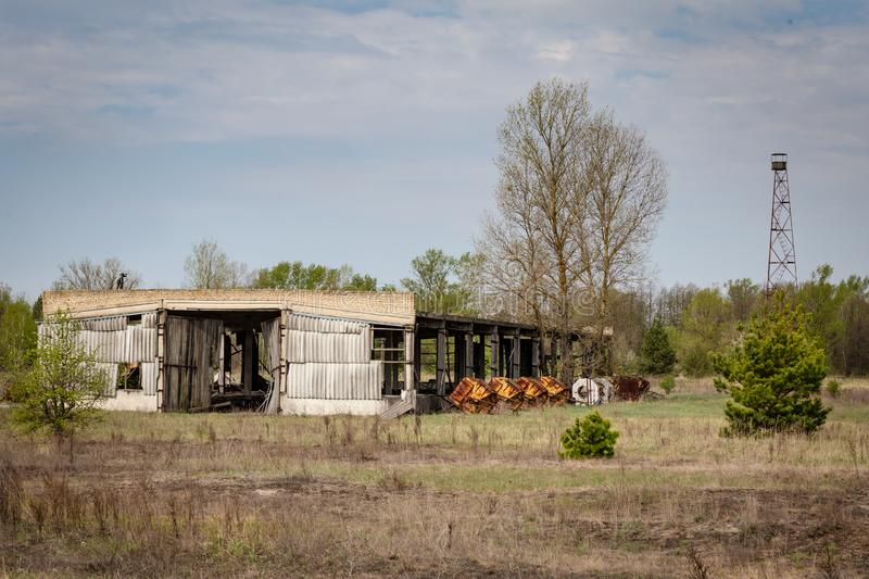 Collapsed farm in Chernobyl. Collapsed farm stable and watchtower in Belarus Chernobyl exclusion zone stock photo