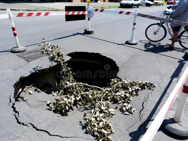 collapsed road surface with big crater below due to washed out road base by storm stock photos