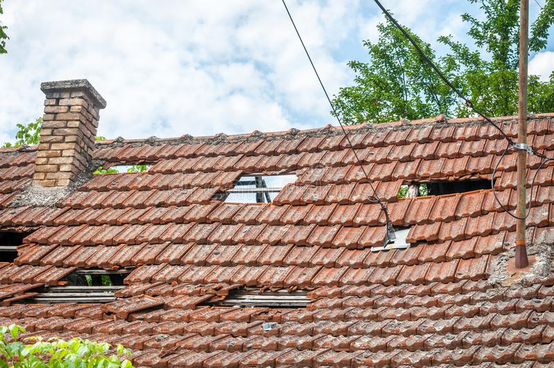 Collapsed roof with tiles on the old ruined and damaged domestic house after earthquake or hurricane storm close up.  royalty free stock photo
