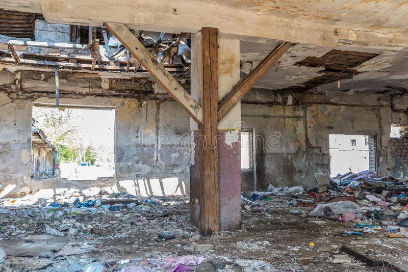 Collapsed roof of the total damaged domestic house indoor from natural disaster or catastrophe with peeled paint and plaster from. The walls stock image