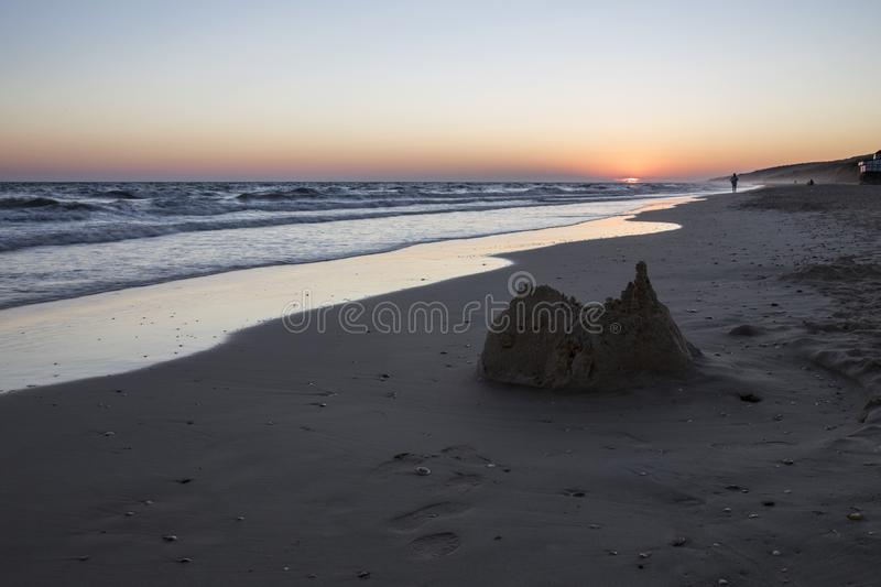 Collapsed sand castle at Matalacanas beach during the magnificent sunrise. Collapsed sand castle atnMatalacanas beach during the magnificent sunrise. Costa de la royalty free stock image