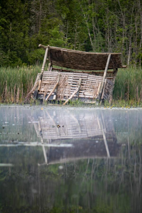 Collapsing Duck Blind Reflected In The River stock images