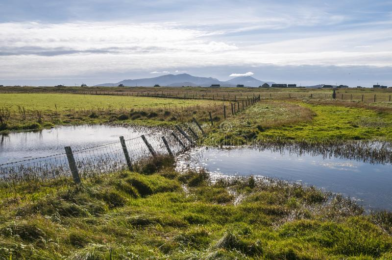 Uist fence. The collapsing fence crossing a waterlogged meadow in the flat landscape of South Uist in Autumn. 26 September 2013 stock images