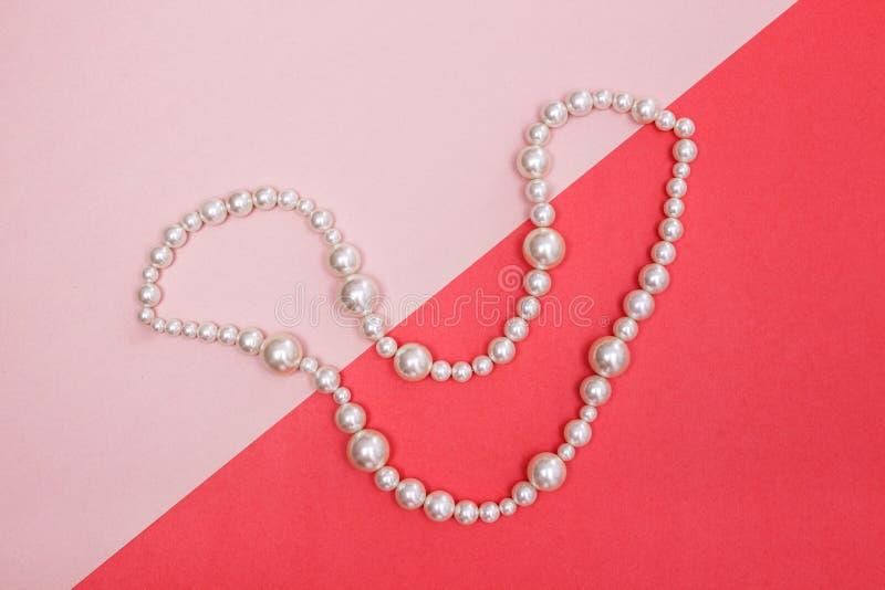 Collar brillante de la perla en fondo rosado fotografía de archivo