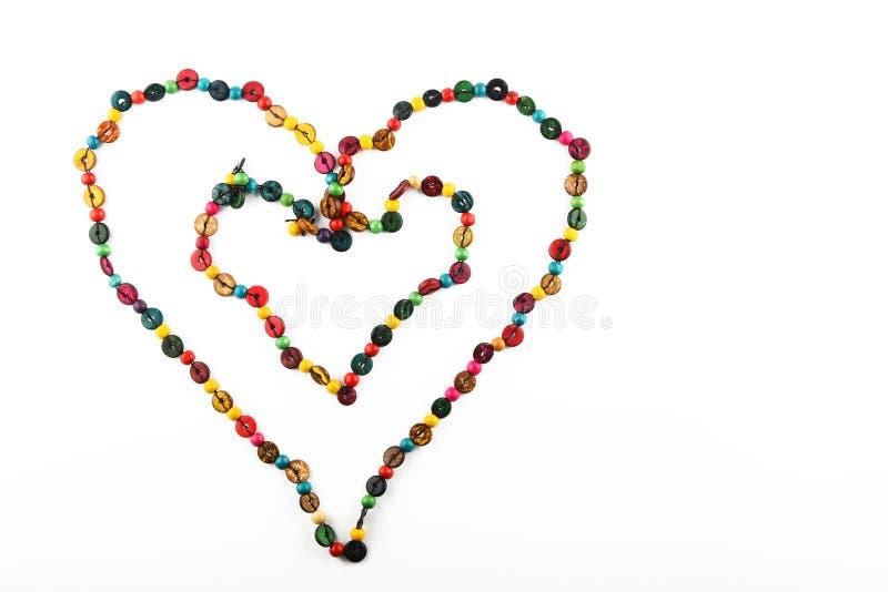 Collar colorido en forma de corazón doble de las gotas aislado en blanco foto de archivo libre de regalías
