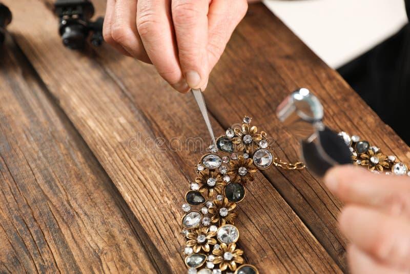 Collar de evaluaci?n del joyero de sexo masculino en la tabla en el taller, primer imágenes de archivo libres de regalías