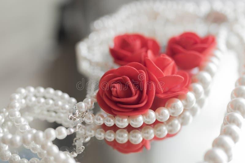 Collar de la perla y rosas rojas imagen de archivo