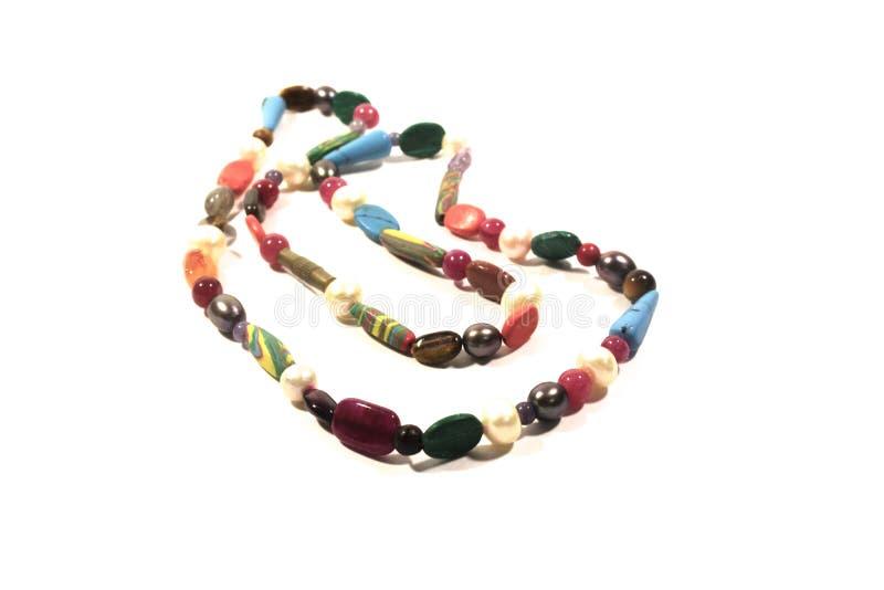 Collar de piedras multicoloras en un fondo blanco imagen de archivo