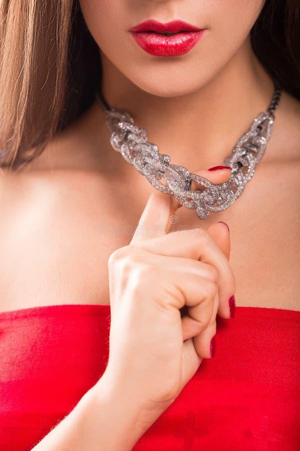 Collar en cuello femenino Muchacha que lleva a cabo las manos Labios rojos atractivos foto de archivo libre de regalías