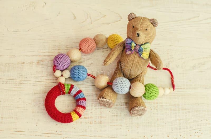 Collar hecho de gotas y de juguetes hechos punto para el bebé que se sienta en una honda imagen de archivo