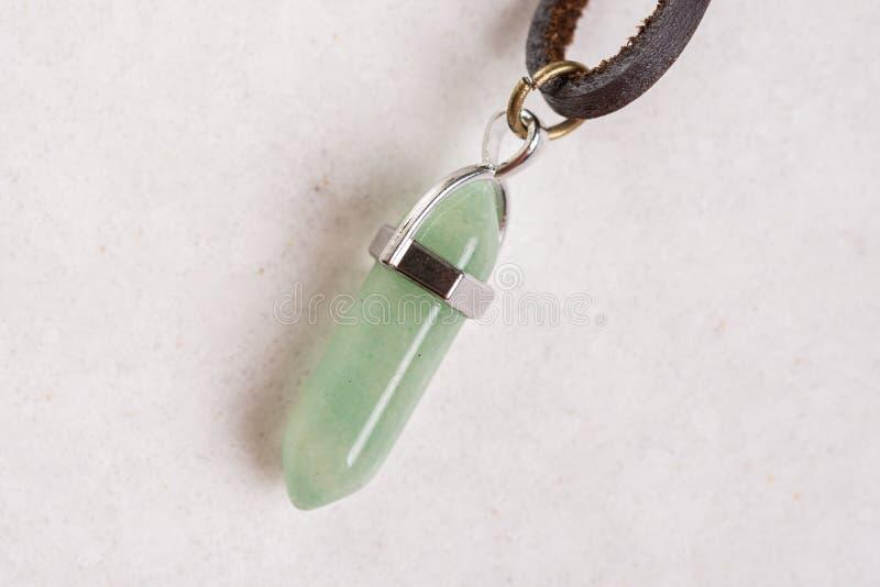 Collar semiprecioso de las piedras del aventurine verde afortunado aislado sobre la piedra de mármol blanca imagenes de archivo