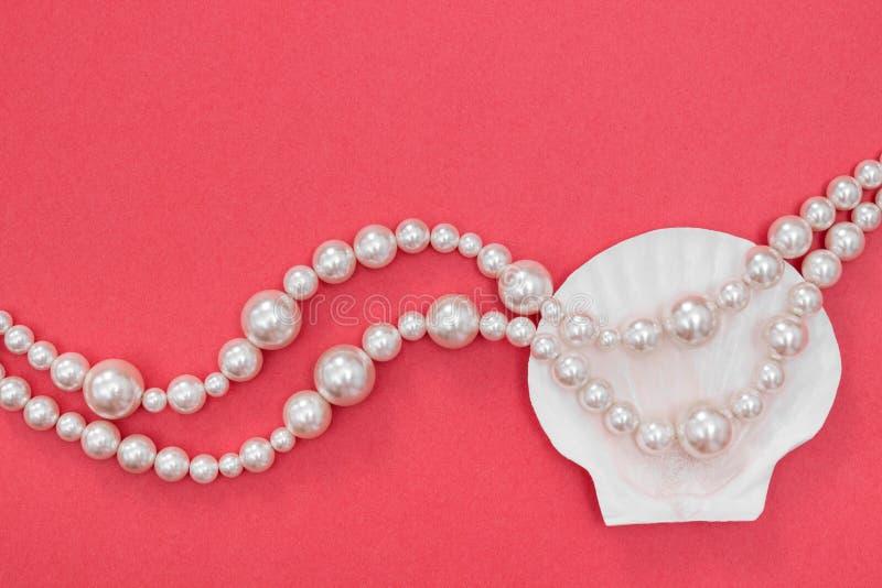 Collar y concha marina de la perla en fondo rosado imágenes de archivo libres de regalías