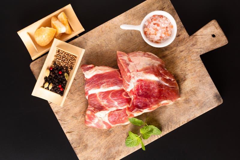 Collare senz'ossa della carne di maiale del pezzo di concetto dell'alimento sul tagliere con la spezia su fondo nero con lo spazi fotografie stock