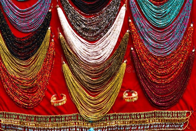 Collares baratos con bufanda roja en Luxor Souq, Egipto fotografía de archivo libre de regalías