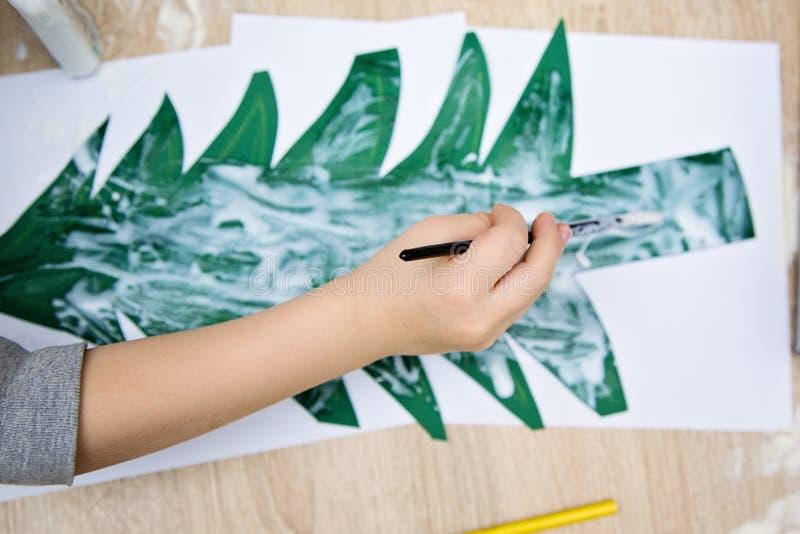 Colle de peinture de main d'enfant en bas âge sur l'arbre de Noël de papier image libre de droits