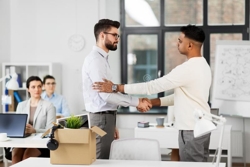 Colleague seeing off sad fired male office worker stock photos