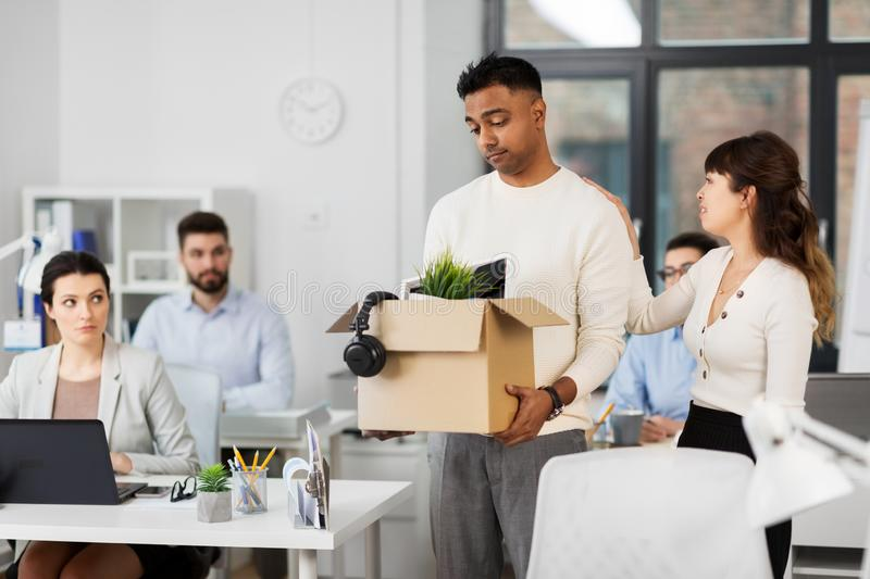 Colleague seeing off sad fired male office worker stock image