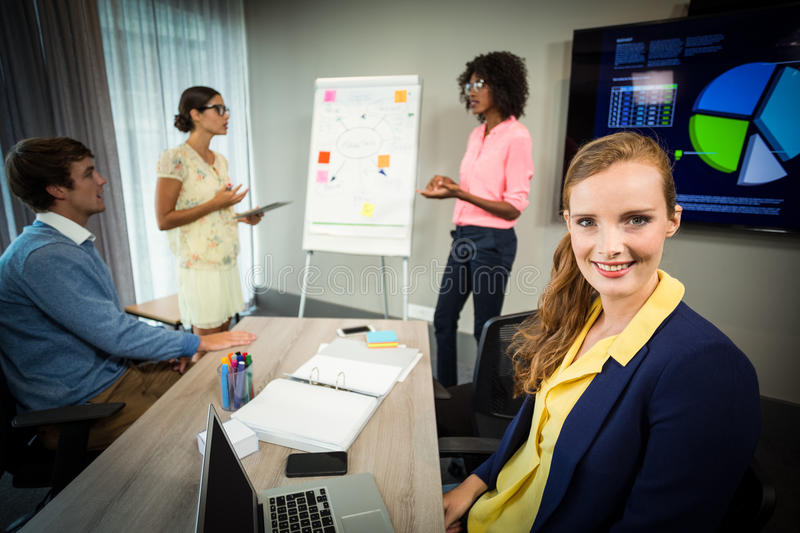 A colleague smiling at camera while coworkers discuss flowchart on whiteboard. In the office royalty free stock photography