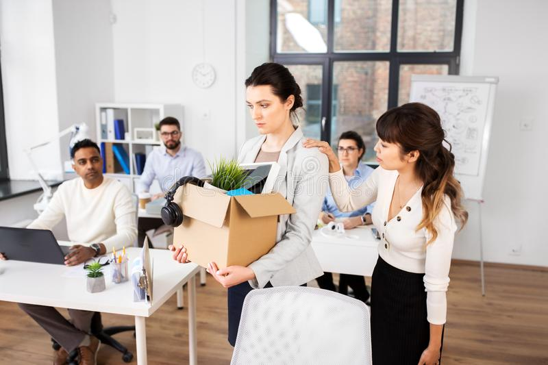 Colleague soothing sad fired female office worker stock images