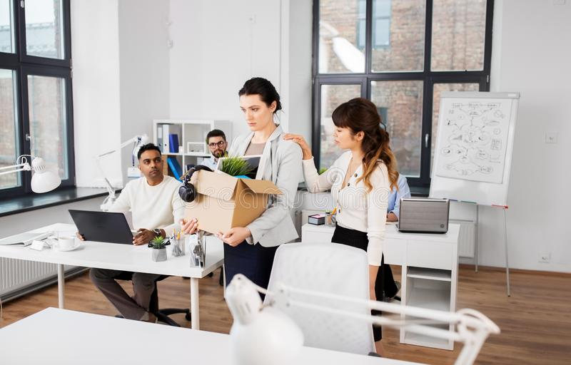 Colleague soothing sad fired female office worker royalty free stock photos