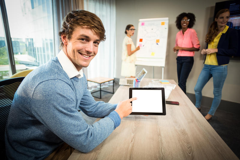 A colleague using digital tablet while coworkers discuss flowchart on whiteboard. In the office royalty free stock photography