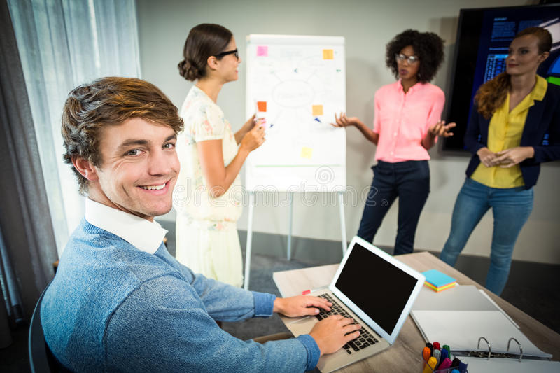 A colleague using laptop smiling at camera while coworkers discuss flowchart on whiteboard. In the office stock images