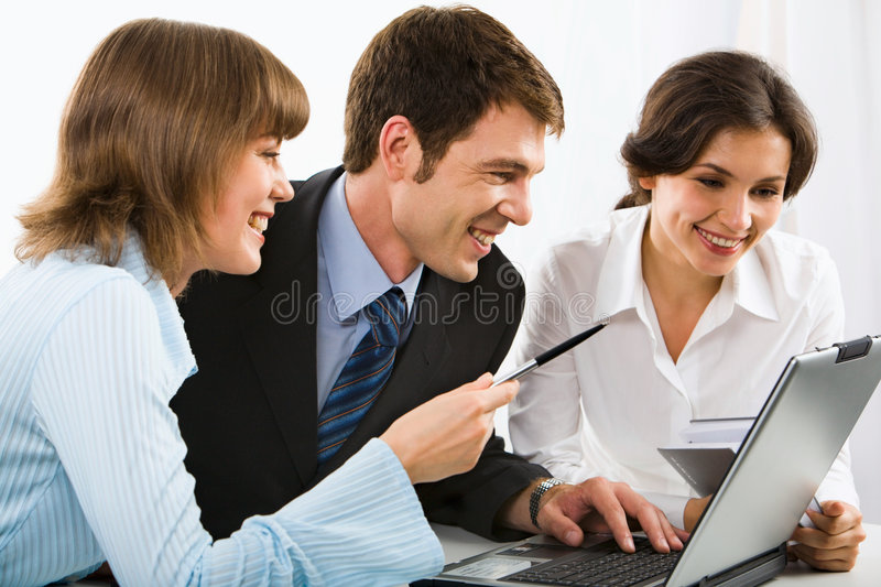 Colleagues. Group of colleagues gathered together around the laptop discussing interesting question