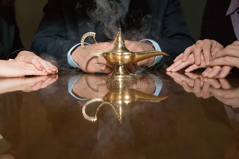 Colleagues around a smoking genie lamp stock images