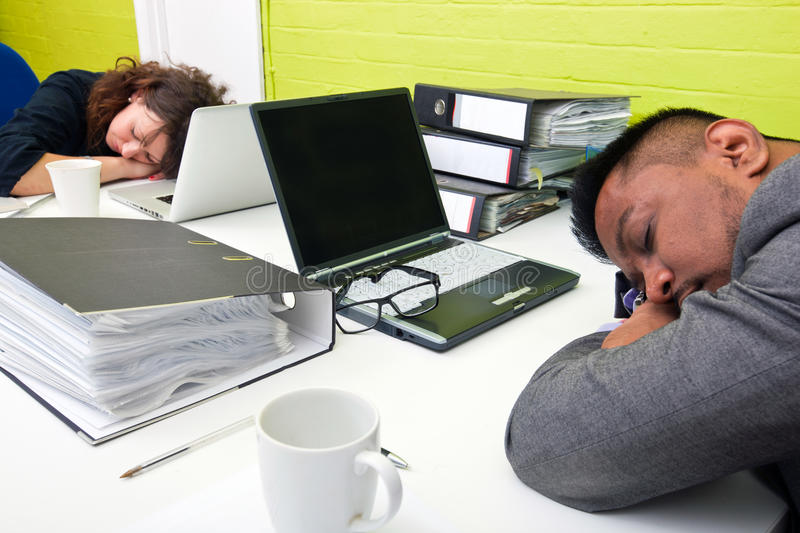 Colleagues asleep at their respective desk stock photography
