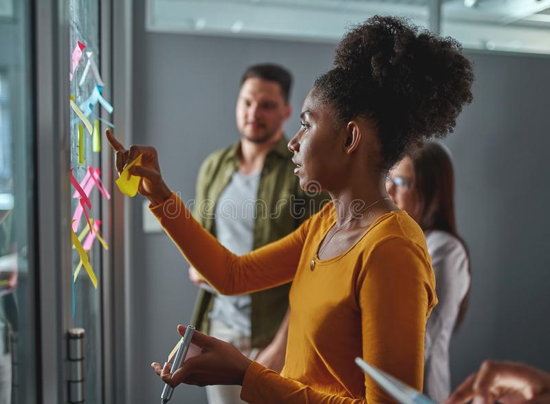 Side view of a young african businesswoman checking and sticking notes on glass at meeting in modern office stock photos