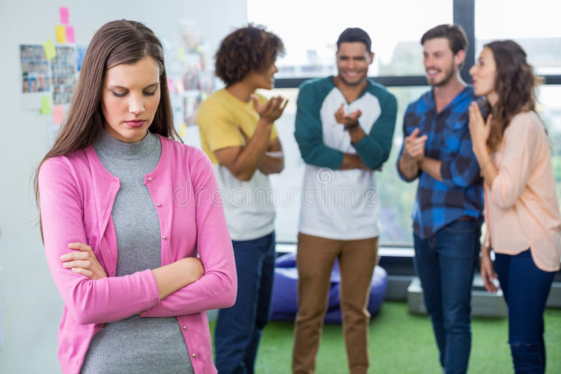 Colleagues bullying a sad female executive stock images