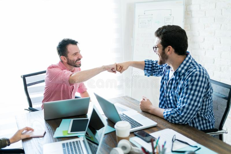 Colleagues Bumping Fist After Profitable Deal stock image