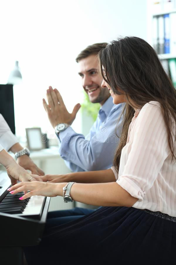 Colleagues enjoying playing synthesizer stock photo