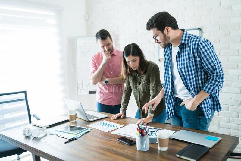 Colleagues Examining Documents In Office stock photography